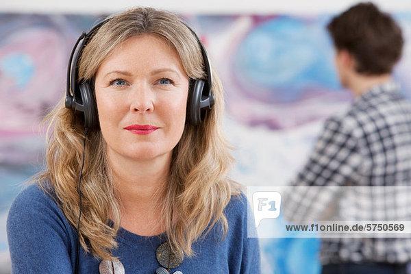Mid adult woman wearing headphones in gallery
