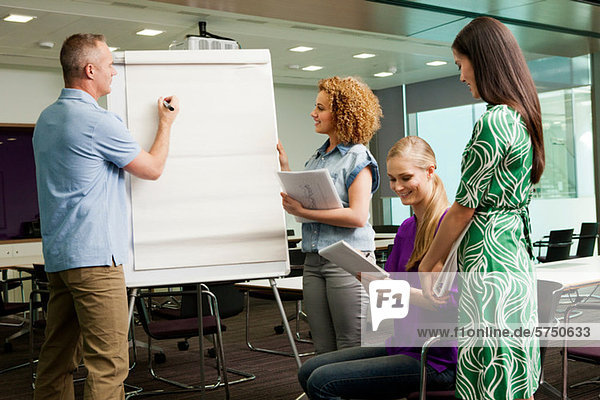Bürokollegen im Whiteboard Meeting im Büro