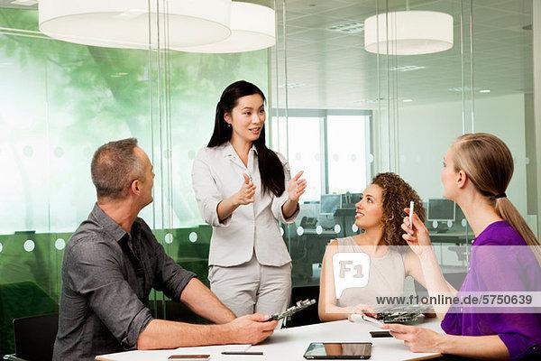 Bürokollegen diskutieren neue Technologien auf dem Schreibtisch