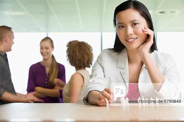 Jungen Architekten sitting at Desk mit Modell-Figuren