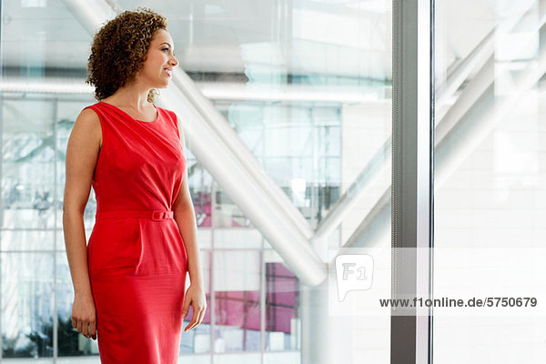 Young businesswoman in red dress in office