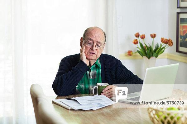 Älterer Mann  der sich Dokumente auf dem Schreibtisch zu Hause ansieht.