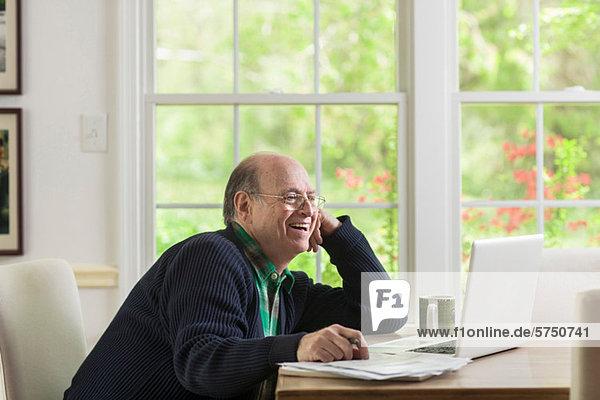 Senior Senioren benutzen Mann Notebook lächeln Wohnhaus
