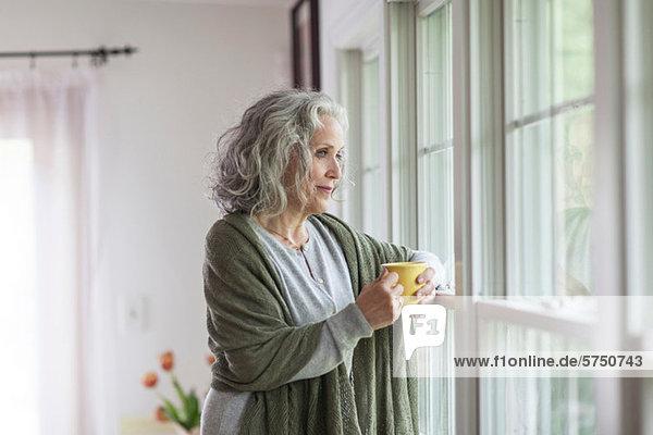 Seniorin mit Blick aus dem Fenster