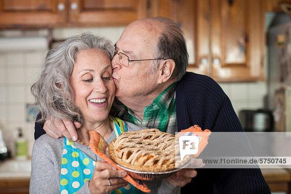 Senior Mann küssende Frau mit frisch gebackenem Kuchen
