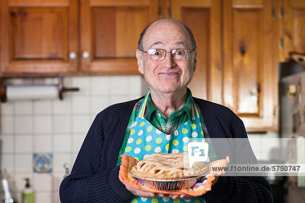 Senior Mann mit frisch gebackenem Kuchen  Portrait