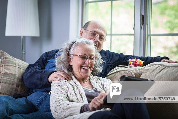 Senior Paar mit digitalem Laptop auf dem Sofa zu Hause