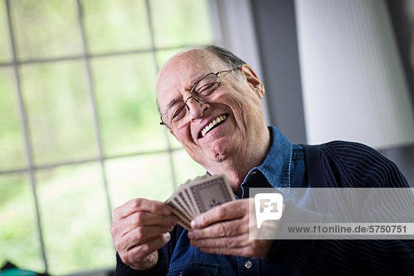 Senior Mann beim Kartenspiel zu Hause