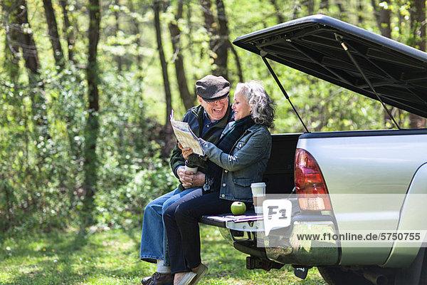 Senior Couple lesen Karte während der Sitzung am Kofferraum im Wald