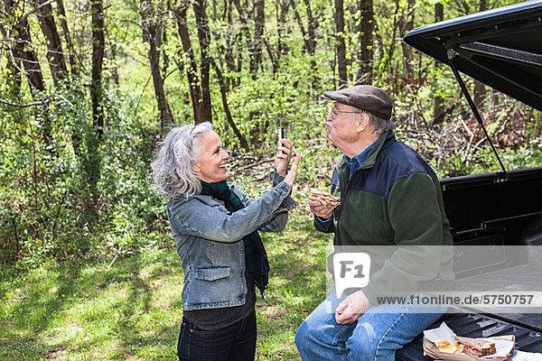 Senior Woman unter Bildmitteilung der Mann sitzt auf Kofferraum