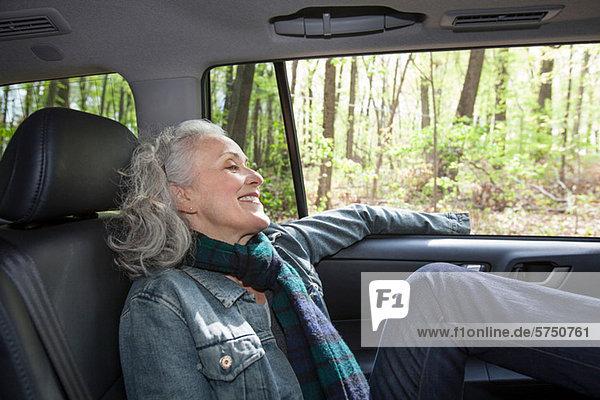 Senior Woman relaxing in Rücksitz des Autos