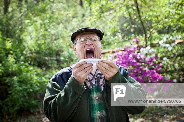 Älterer Mann im Begriff  draußen zu niesen.