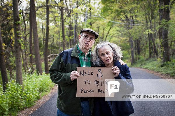 Seniorenpaar mit Schild im Wald  Portrait