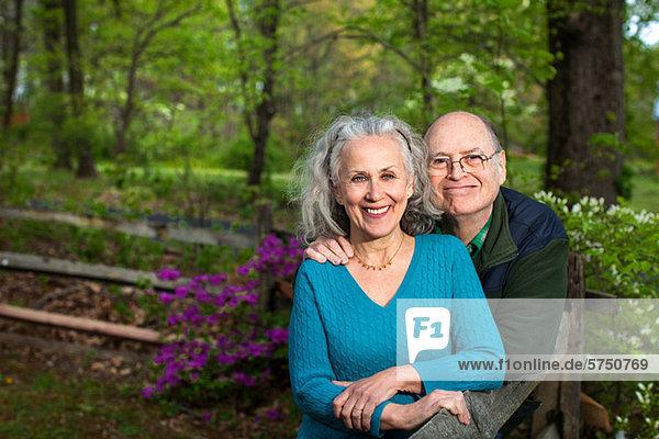 Seniorenpaar im Wald sitzend  lächelnd  Portrait