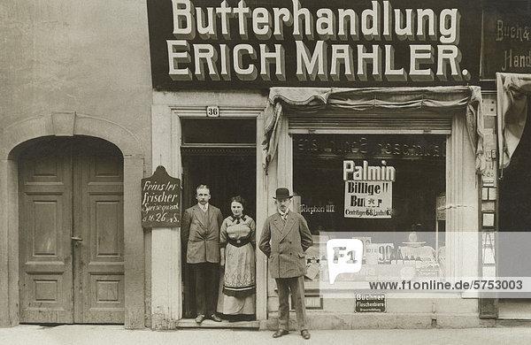 Historische Aufnahme eines Ladenbesitzers vor seinem Lebensmittelladen