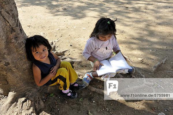 Two girls with exercise books sitting in the shade of a tree  Lomas de Santa Faz slum  Guatemala City  Guatemala  Central America