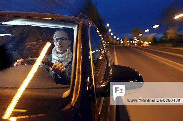 Junge Frau fährt abends mit einem Auto über eine beleuchtete Straße