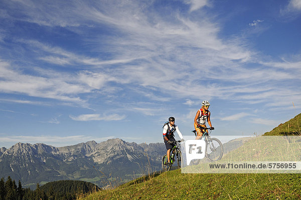 Mountain bikers at Kraftalm alp  Wilder Kaiser massif at back  Mt Hohe Salve  Kitzbuehel Alps  Tyrol  Austria  Europe