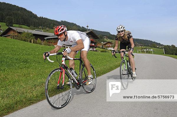 Couple riding racing bikes  Kelchsau  Kitzbuehel Alps  Tyrol  Austria  Europe