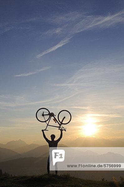 Mann hält Rennrad in die Höhe  Kraftalm  Hohe Salve  Kitzbühler Alpen  Tirol  Österreich  Europa