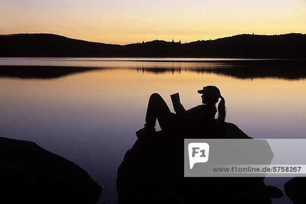 Eine junge Frau liest bei Sonnenuntergang auf einem Felsen Küstenlinie auf Stand See  an einem kühlen Herbst Nacht  Algonquin Provincial Park  Ontario  Kanada.