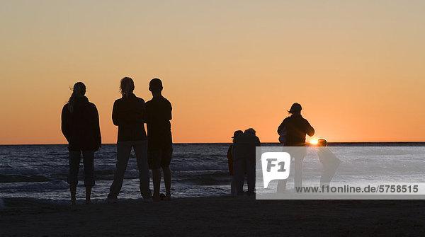Eine Familie wacht den Sonnenuntergang über den Huronsee in Sauble Beach  Ontario  Kanada.