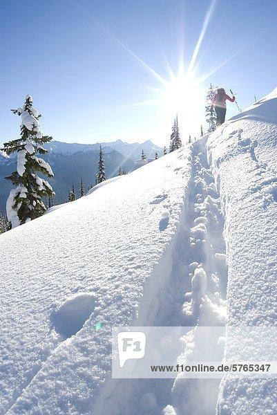 Eine junge Frau Skifahrer steigt Corbin Pass in der Nähe von Revelstoke in British Columbia