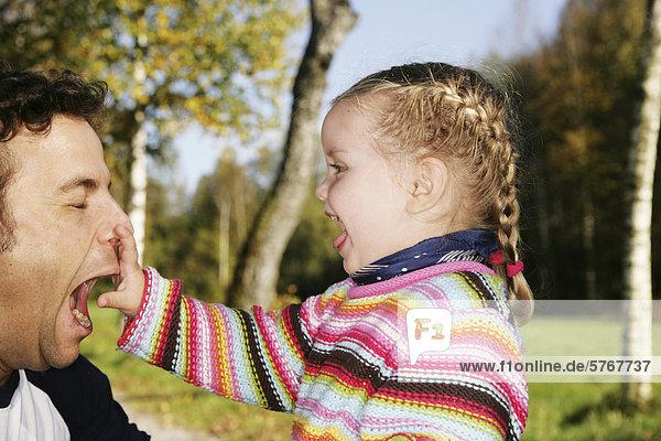 Vater und Tochter (3 Jahre) albern rum