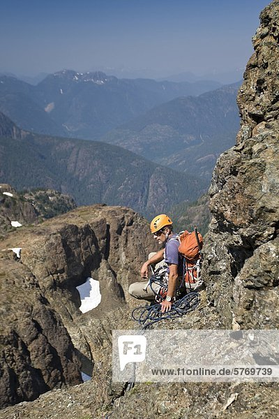 A climber takes a break and waits for fellow climbers to catch up to him while ascending Elkhorn Mountain in Strathcona Park  Vancouver Island  British Columbia  Canada
