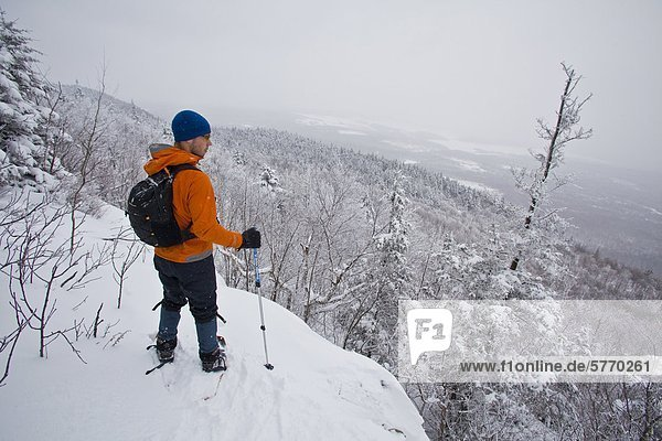 Ein junger Mann  Schneeschuhwandern im frischen Powder in den östlichen Townships auf Mt. Schinken  Quebec  Kanada