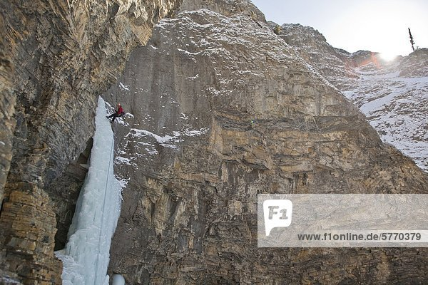 A man rappelling after free soloing the  Fang & Fist WI5  Ghost River Valley  Alberta  Canada