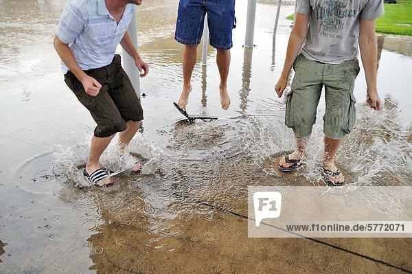 Drei junge Männer springen in Pfützen Drei junge Männer springen in Pfützen