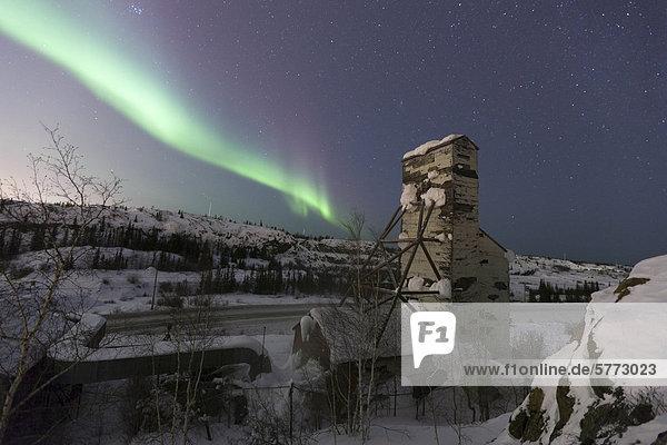 Die Aurora Borealis oder Nordlichter  über einen verlassenen Kopf Rahmen von Giant Mine  außerhalb Yellowknife  Northwest Territories  Kanada.