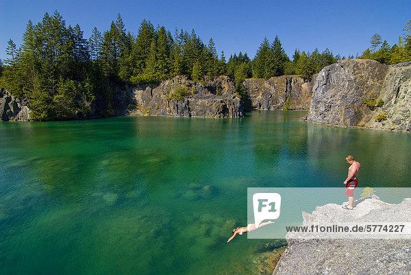 Junges Paar genießen Sie eintauchen in die spektakuläre Smaragdwasser der Heisholt See auf Texada Island  an der Sunshine Coast in der Region Vancouver  Küste und Berge von British Columbia  Kanada