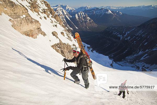 Zwei männliche Hinterland Skifahrer Bootpack bis eine steile Gesicht der Nordwand des Mt. Stanley  Kootenay Nationalpark  British Columbia  Kanada