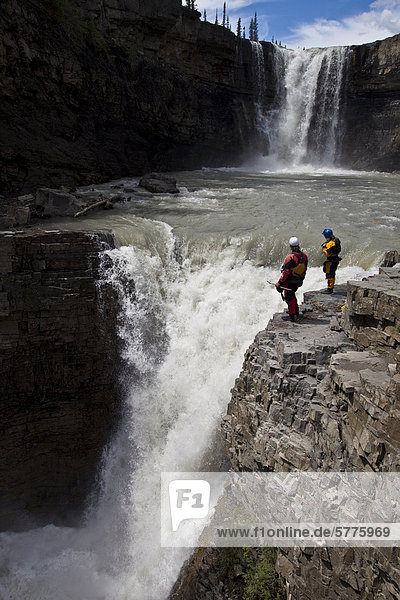 Two male kayakers scout a big waterfall on the Bighorn river  Nordegg  Alberta  Canada