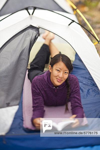 Eine glückliche  gesunde Frau tut etwas zu lesen beim camping in Jasper Nationalpark  Alberta  Kanada