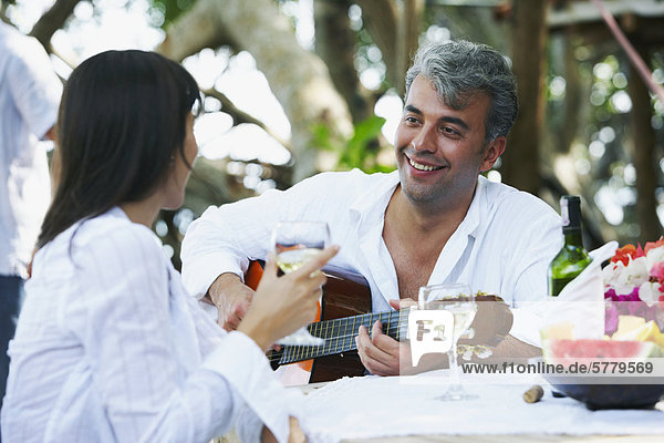 South American man playing guitar for wife