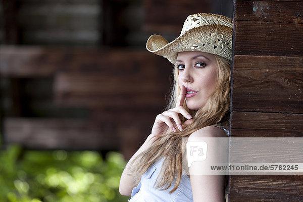 Junge Frau mit Cowboyhut und Schweigegeste  Portrait  Western Style