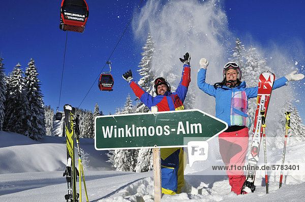'Skiers with sign ''Winklmoos-Alm'' and gondola lift or cable car  Reit im Winkl  Chiemgau region  Bavaria  Germany  Europe'