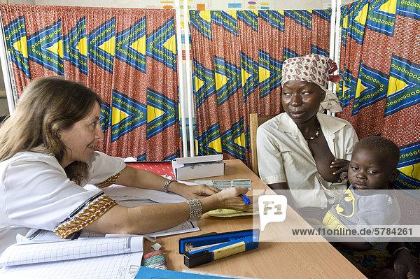 Ärztin berät eine HIV-positive Mutter wie sie ihr Kind vor der Übertragung des Virus schätzen kann  Ambulanz in Quelimane  Mosambik  Afrika