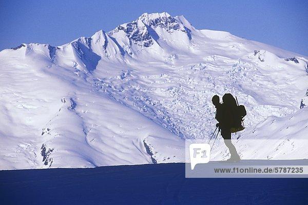 Mann hält zum Anzeigen von Mount Tisiphone  Küste-Strecke  auf der Lillooet Icefield Traverse  British Columbia  Kanada.