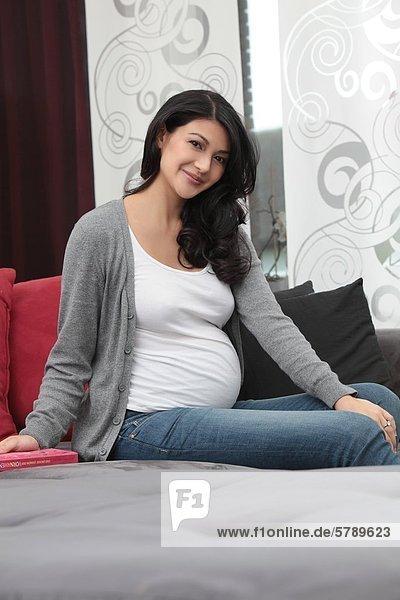 Lächelnde schwangere Frau sitzt auf der Couch