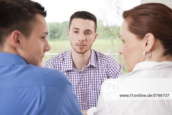 Zwei junge Männer und eine Frau im Meeting