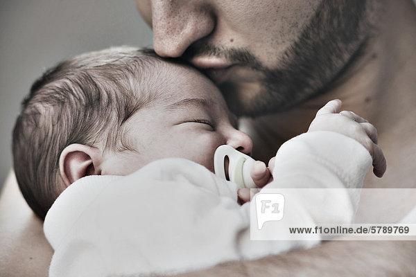 Vater küsst zwei Wochen altes Baby