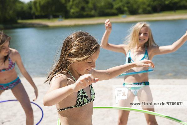 Drei Mädchen in Bikinis mit Hula-Hoops an einem Badesee