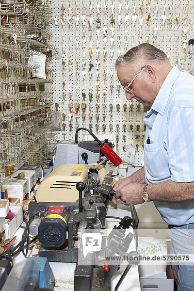 Side view of senior locksmith making key in store