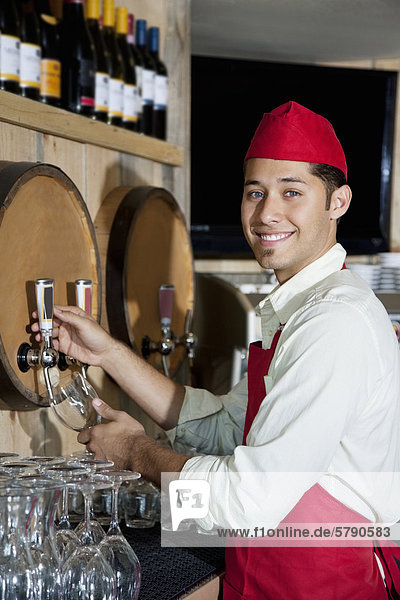 Portrait of a young waiter standing by drinks tap