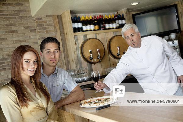 Porträt eines jungen Paares mit Küchenchef hält Glas Wein