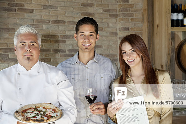 Portrait of mid adult chef holding pizza with young couple